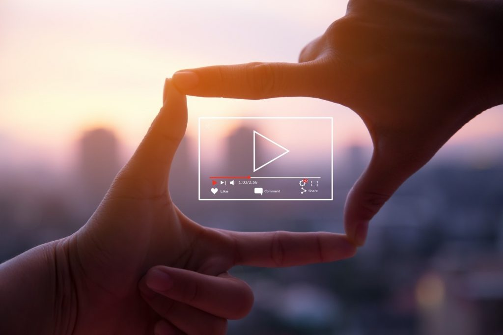 A picture containing person, hand making a square shape and a box with a play button inside it.