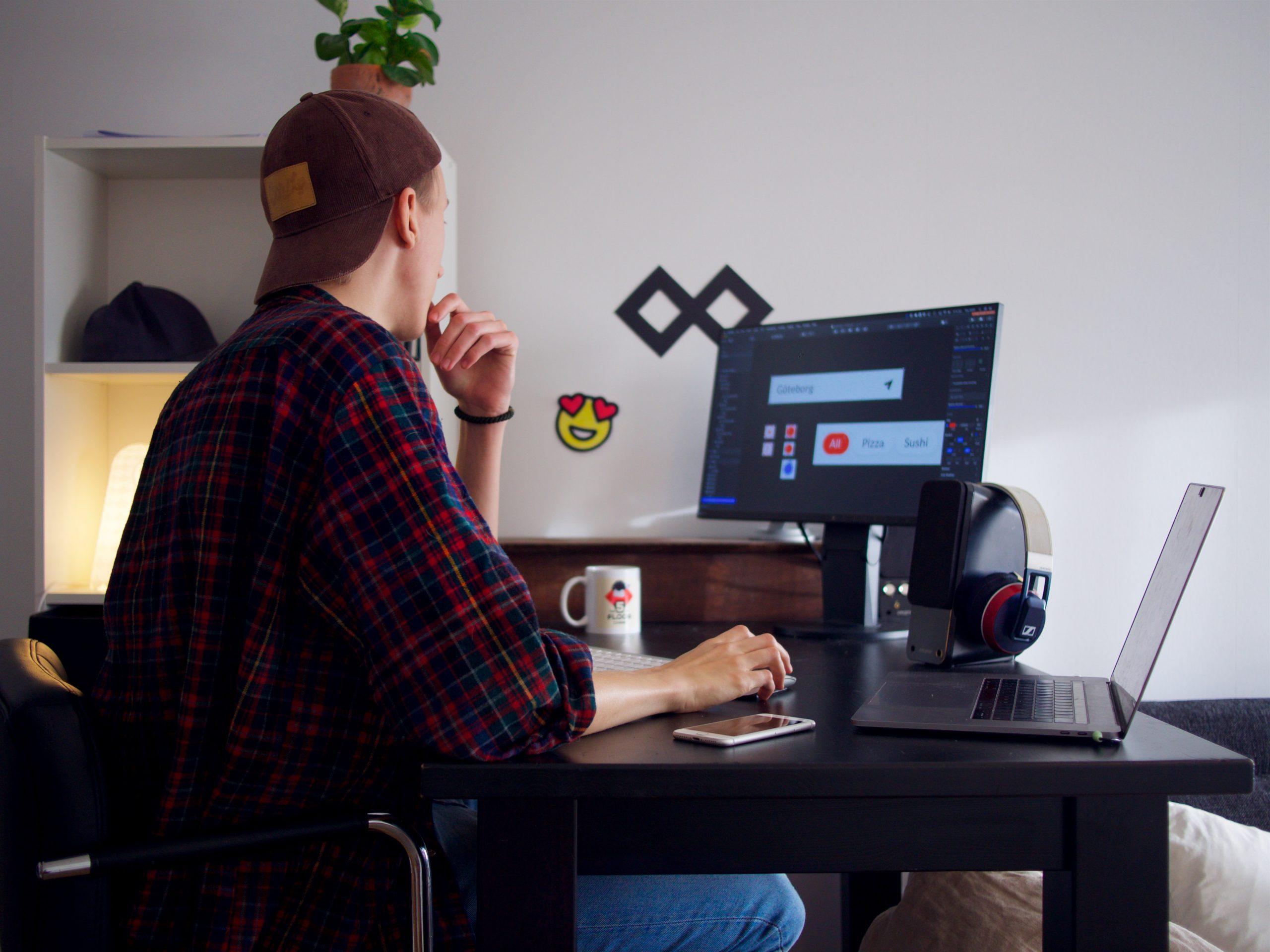 man sitting near table using computer